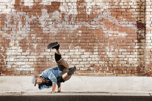 A young man doing a breakdance move balancing on his hands on the street of a city.の写真素材 [FYI02250949]