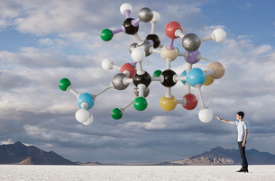 A teenage boy looking upwards at a molecular structure in the air above him.の写真素材 [FYI02250952]