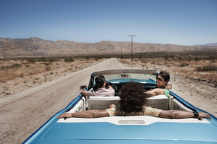 Three young people in a pale blue convertible car, driving on the open road across a flat dry plain,の写真素材 [FYI02250960]