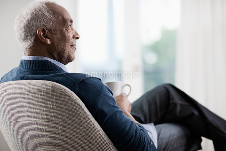 A mature man with grey hair leaning back in a chair, relaxing with a cup of tea or coffee.の写真素材 [FYI02250988]