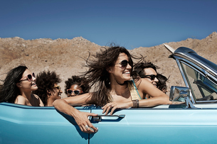 A group of friends in a pale blue convertible on the open road, driving across a dry flat plain surrの写真素材 [FYI02250992]
