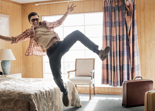 A young man in sunglasses leaping in the air in a motel room.の写真素材 [FYI02250996]