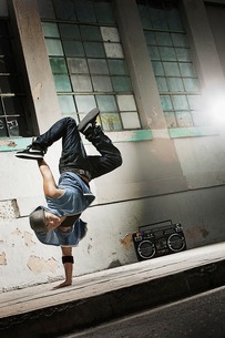A young man breakdancing on the street of a city, doing a one handed handstand.の写真素材 [FYI02251000]