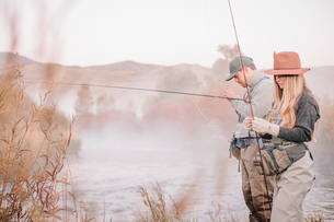 A couple fishing on a riverbank, tying the flies to the hooks for fly fishing.の写真素材 [FYI02251002]