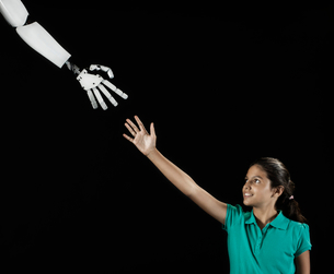 A girl reaching up to touch a robotic hand.の写真素材 [FYI02251008]