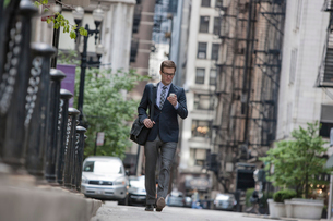 A working day. Businessman in a work suit and tie on a city street checking his smart phone.の写真素材 [FYI02251011]