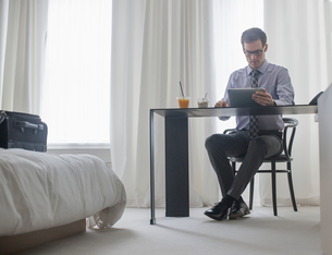 A working day. A man seated at a laptop computer, working in a hotel bedroom.の写真素材 [FYI02251019]