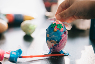 A child decorating eggs at Easter with glitter, glue and paint.の写真素材 [FYI02251026]