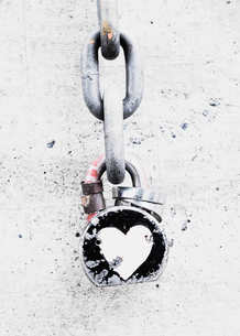 Decorated lock and chain on a wall, a symbol of a bond of affection of love, heart shaped metal.の写真素材 [FYI02251032]