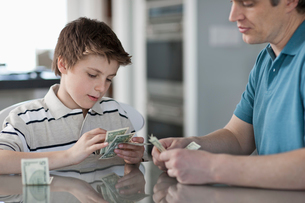 A man and a boy seated at a table, counting and handling cash.の写真素材 [FYI02251033]