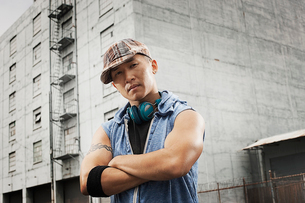 A young person in a denim sleeveless shirt, arms folded looking at the camera.の写真素材 [FYI02251053]