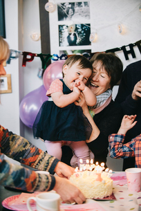 A family gathered to celebrate a one year old girl's birthday party. A cake with lots of candles.の写真素材 [FYI02251059]