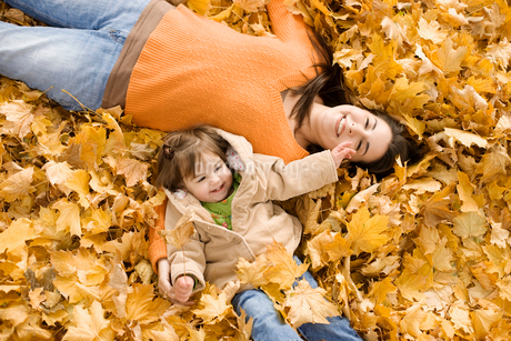 A woman and young child in fallen autumn leaves.の写真素材 [FYI02251061]
