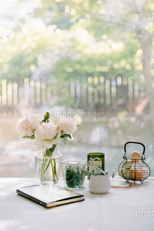Vase with white roses, notebook and jars with herbs, and a basket of fresh eggs.の写真素材 [FYI02251071]