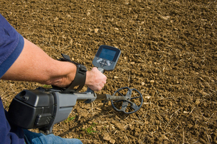 A man holding a metal detector just above the ground in a ploughed field, searching for metal objectの写真素材 [FYI02251075]
