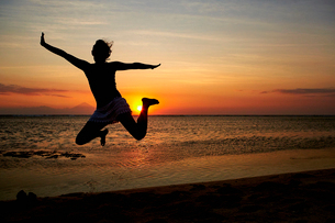 Silhouette of a woman jumping in the air, seen against a sunset sky.の写真素材 [FYI02251079]