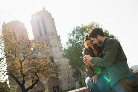 A couple side by side looking a a smart phone screen outside Notre Dame cathedral in Paris.の写真素材 [FYI02251095]