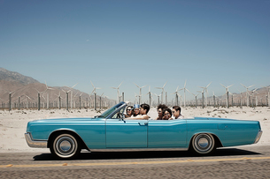 A group of friends in a pale blue convertible on the open road, driving across a dry flat plain surrの写真素材 [FYI02251099]