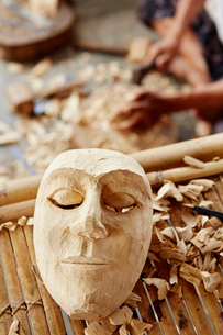 A traditional wooden mask being made in a carver's workshop.の写真素材 [FYI02251103]