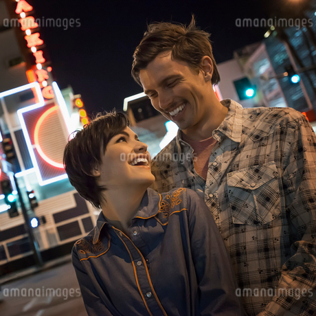 A couple, man and woman side by side in a city street at night. Neon signs.の写真素材 [FYI02251115]