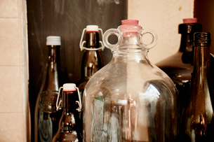 A shelf of bottles and jars, one large double handled jar with a stopper and bottles with lids.の写真素材 [FYI02251129]