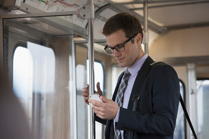 A working day. Businessman in a work suit and tie in a train carriage, checking his phone.の写真素材 [FYI02251140]