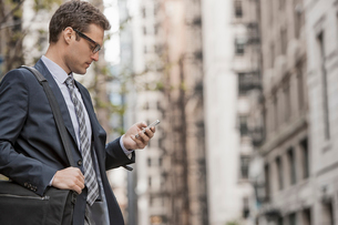 A working day. Businessman in a work suit and tie on a city street, using his phone.の写真素材 [FYI02251152]