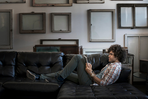 Loft decor. A wall hung with blank canvases. A man on a sofa using a digital tablet.の写真素材 [FYI02251153]