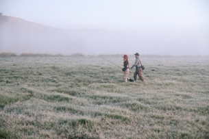 Two people walking across a meadow in early morning mist carrying fishing rods.の写真素材 [FYI02251158]