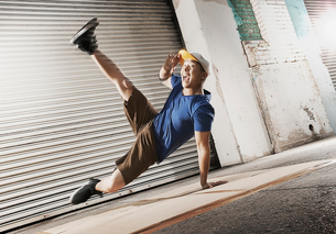 A young man breakdancing on the street of a city, balancing on one hand with his legs apart.の写真素材 [FYI02251171]