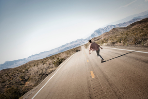 A young man riding down a tarmac road in the desert on a skateboard.の写真素材 [FYI02251178]