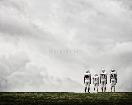 A group of four football players in sports uniform, three tall figures and one shorter team player.の写真素材 [FYI02251180]