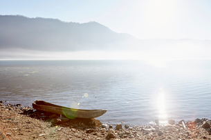 Sunlight on the water of a mountain lake, and a dug out canoe on the shore.の写真素材 [FYI02251196]