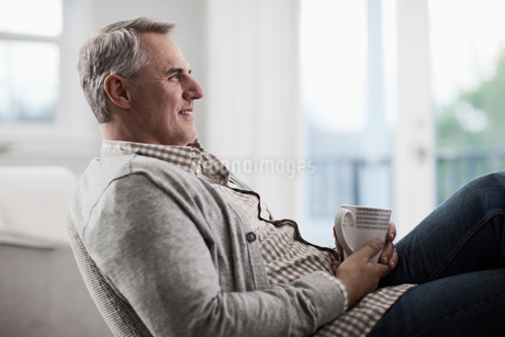 A mature man with grey hair leaning back in a chair, relaxing with a cup of tea or coffee.の写真素材 [FYI02251197]