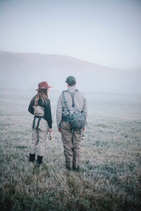 Two people walking across a meadow in early morning mist carrying fishing rods.の写真素材 [FYI02251209]