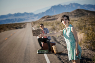 A young couple, man and woman, on a tarmac road in the desert hitchiking, with a sign saying Vegas oの写真素材 [FYI02251210]