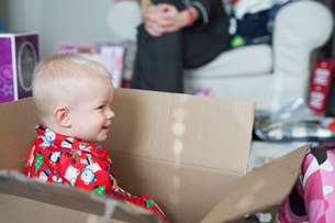 A young boy sitting in a large cardboard box, among wrapping paper and presents.の写真素材 [FYI02251216]