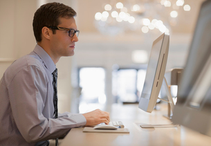 A businessman in shirt and tie seated at a computer in a business centre or office.の写真素材 [FYI02251226]