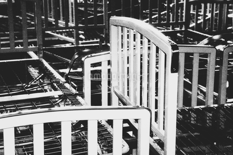 Empty hospital bed frames, stacked up in a pile in an empty room.の写真素材 [FYI02251230]