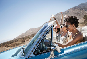 Three young people in a pale blue convertible car, driving on the open road across a flat dry plain,の写真素材 [FYI02251233]
