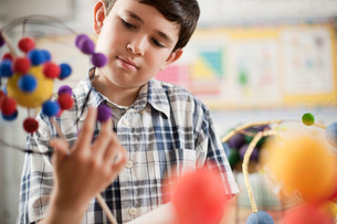 A boy examining a molecular structure in a science lesson.の写真素材 [FYI02251243]