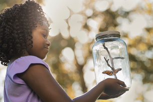 A girl holding a glass jar with a butterfly inside it.の写真素材 [FYI02251253]