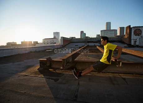 A man in exercise clothes on a rooftop overlooking the city, doing bench shoulder push ups.の写真素材 [FYI02251299]