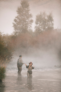 A couple, a man and woman standing in mid stream fly fishing in a river.の写真素材 [FYI02251300]