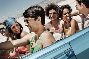 A group of friends in a pale blue convertible on the open road, driving across a dry flat plain surrの写真素材 [FYI02251312]