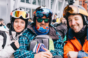 Three people, a young woman and two men in ski gear, in a row on a ski-ing holiday.の写真素材 [FYI02251322]