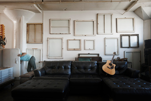 Loft decor. A wall hung with pictures in frames, reversed to show the backs. A man at an open fridgeの写真素材 [FYI02251326]