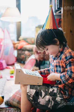 A boy unwrapping presents at a birthday party.の写真素材 [FYI02251333]