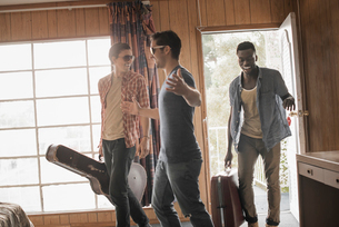 Friends, three young men in a motel room, carrying cases and a guitar.の写真素材 [FYI02251334]