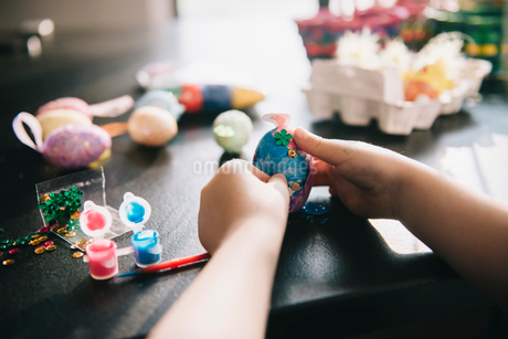 A child decorating eggs at Easter with glitter, glue and paint.の写真素材 [FYI02251337]